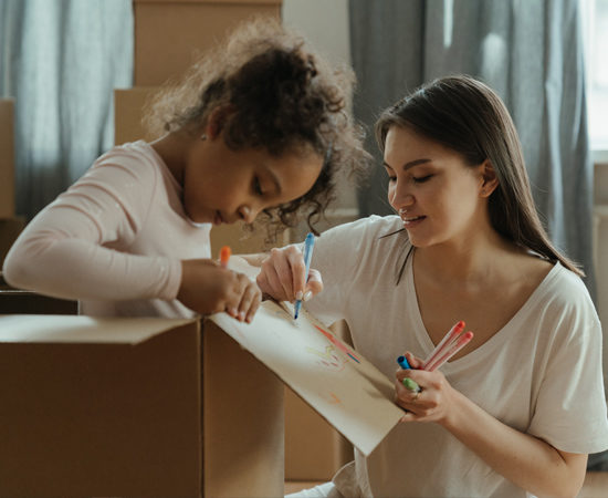 man teaching her daughter how to draw on a box