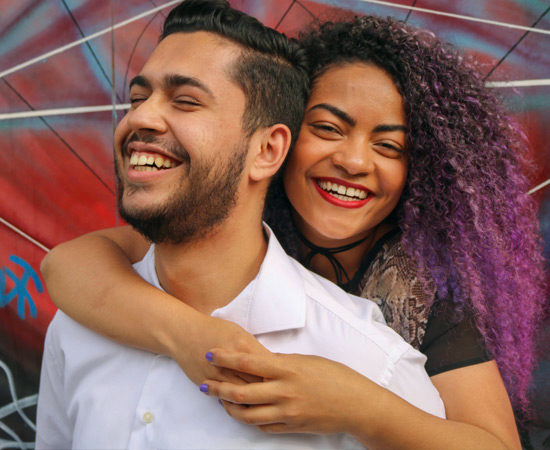 a young couple smiling and hugging