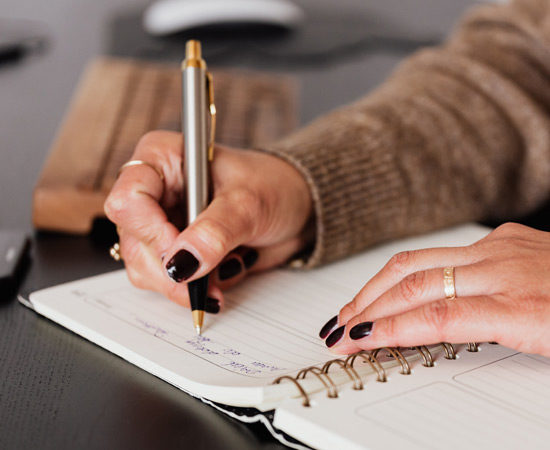 woman with black nail polish writing in a notebook
