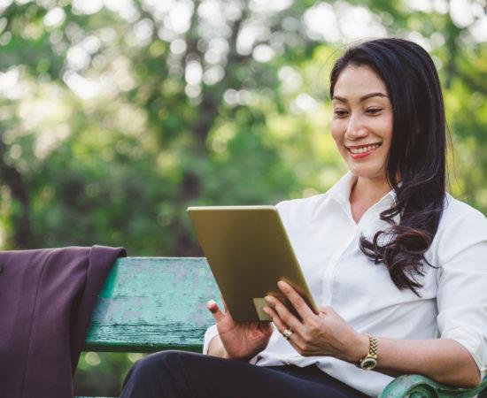 Asian woman reading her ipad